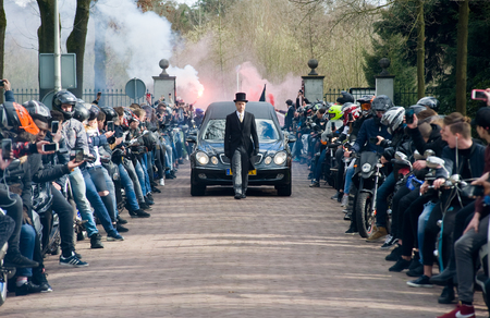 mortician: ENSCHEDE, THE NETHERLANDS - MARCH 17, 2017: Members of a motorgang making a lane during a funeral procession. It is a tribute because one of their members parished in a crash. Editorial