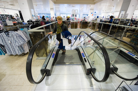 holland: ENSCHEDE, THE NETHERLANDS - APRIL 13, 2017: A woman on the moving staircase in clothes store C&A after it has been reopened. Editorial