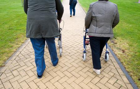 An elderly couple walking behind their walking frames