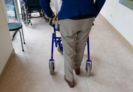 An elderly man walking behind his walking frame Stock Photo