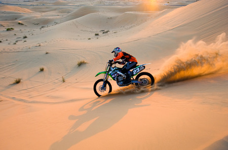 ABU DHABI, UNITED ARAB EMIRATES - JAN 01, 2018: A man on a dirt bike is riding on the hills in the desert in the United Arab Emirates.