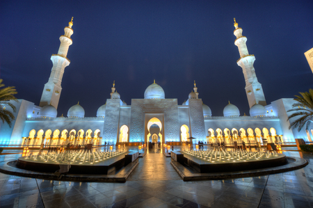 ABU DHABI, UNITED ARAB EMIRATES - DEC 31, 2017: Exterior of the Sheikh Zayed Mosque in Abu Dhabi in twilight. It is the largest mosque in the country. HDR picture.