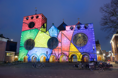 ENSCHEDE, NETHERLANDS - DEC 22, 2017: : In the centre of the Dutch city Enschede the Jacobus chuch is being lighted by a beamer with changing colours because of christmas time.