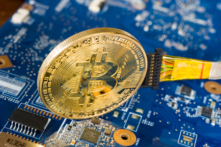 Wired bitcoin standing on the electronic motherboard of a laptop