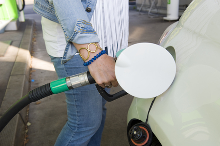 A woman is filling her car with fuel at a filling station