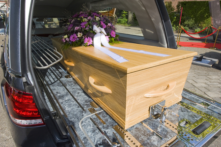 A coffin with a flower arrangement in a funeral car Stock fotó