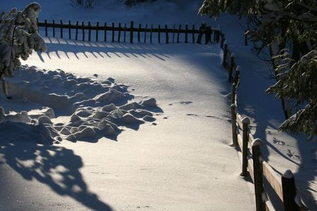 fenced in: The sun of a winters day draws sharp shades in the fenced in snowy scenery on the