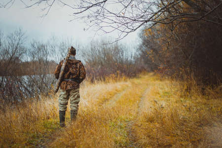 A man in camouflage clothing with a gun in a case on his shoulder, standing back on the forest road. Autumn hunting. Stockfoto