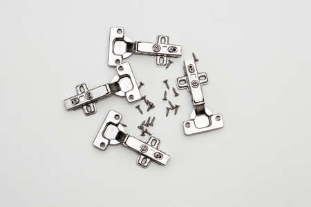 Four furniture awnings and screws on a white background. Steel furniture fittings.