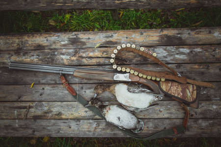 Russia, Kholmogory-October 17 2019 A double-barreled vertical rifle, a bandolier and two dead wild ducks on a wooden table. Autumn duck hunting. The view from the top.