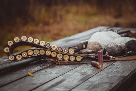 Russia, Kholmogory-October 17 2019 Bandolier with cartridges and two cartridges on a wooden table in the foreground. In the background is a trophy (two wild ducks) and a double - barreled shotgun. Autumn hunting for wild birds.