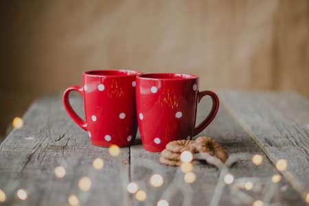 Atmosfera accogliente, biscotti al cioccolato e tazze rosse da fanciulla, ghirlande di luci in primo piano. Tavolo rustico in legno.