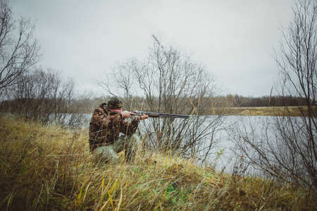 Hunter with a double-barreled gun crouched and makes a shot. Autumn hunting.