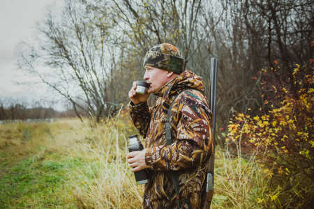 Hunter in camouflage clothing with a gun in a case drinking tea . The hunter stands in profile. Autumn hunting for wild ducks.