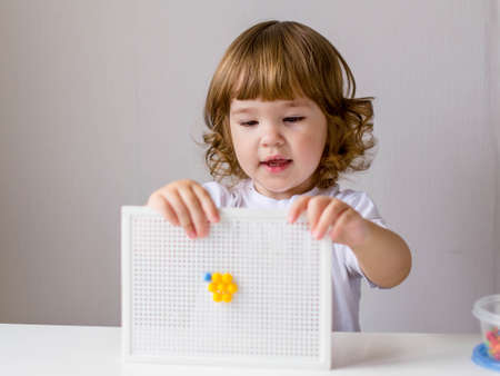 A little curly-haired girl in a white t-shirt plays at a white table in a multicolored plastic mosaic. The child shows the result of his creativity. The concept of early education, the development of fine motor skills.