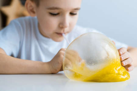 A boy in a white T-shirt at a white table plays a slime. Child inflates bubble slime. Banco de Imagens