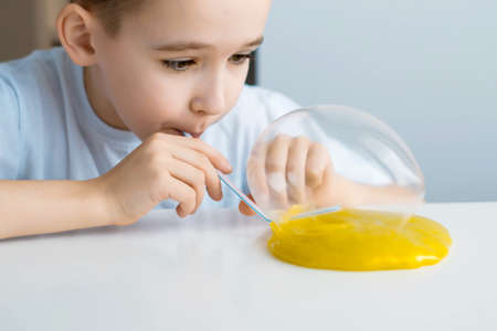 A boy inflates a ball from a slime. Close-up child in a white T-shirt at a white table plays a slime.