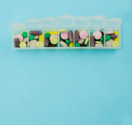 pill box with pills and vitamins. View from above. Plastic pill box on a blue background.