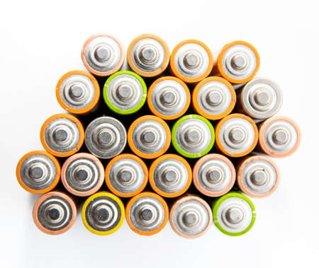 Close up of positive ends of colorful discharged batteries of different sizes and formats, top view, copy space. Used alkaline battery on a white background. Dangerous garbage concept.