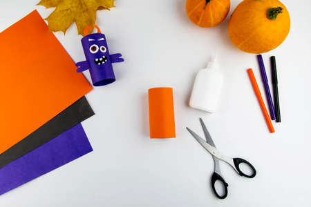 Halloween decoration. DIY and kids creativity concept. Step by step instructions: make a monster from a toilet roll of orange and purple paper. Step 6 is an intermediate result.