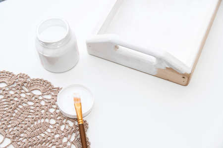 Painting the wooden tray white. Home creativity concept.