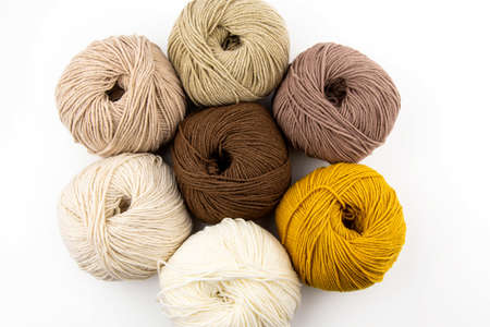 Balls of yarn for knitting brown flowers in a metal basket on a white background.