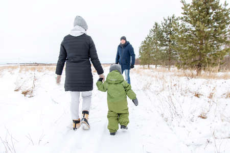 Winter walk through the family park. Mom and baby go to daddys hand.