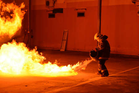 rehearse: Man in fire show after Firefighters training, Rehearse of firefighters from cooking. The burning gas tank and Smoke from burning. Stock Photo