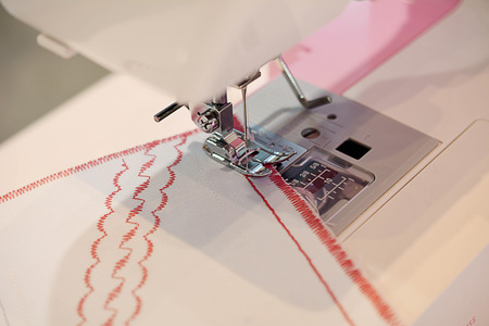 stitchwork: Sewing machine, A sewing machine is a machine used to stitch fabric and other materials together with thread. Sewing machines were invented during the first Industrial Stock Photo
