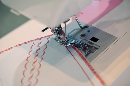 zigzagger: Sewing machine, A sewing machine is a machine used to stitch fabric and other materials together with thread. Sewing machines were invented during the first Industrial Stock Photo