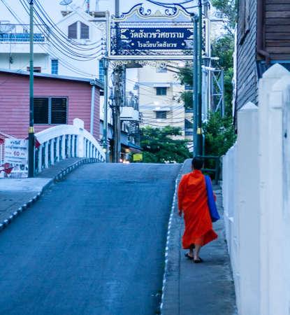 Budist monk walking alone in a Bangkok street in Thailand