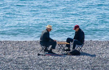 Backgammon match between to elders in the peeble beach in Nice Stockfoto