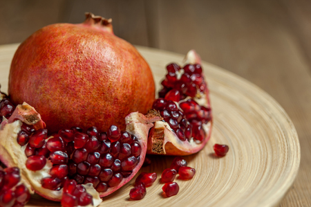 open pomegranate and flat plate on wooden table Imagens