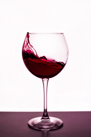 splashes of red wine in a wineglass