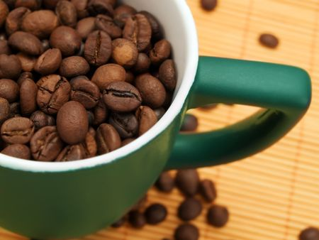 Coffee beans in a green cup Stock Photo