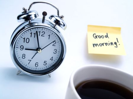 An alarm clock, a cup of coffee and a yellow note