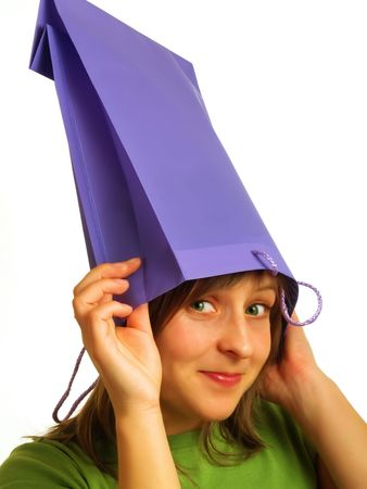 A pretty blond girl put a violet shopping bag on her head photo
