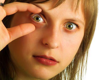 oculista: Una hermosa muchacha rubia est� mostrando uno de sus ojos a un oculist  Foto de archivo