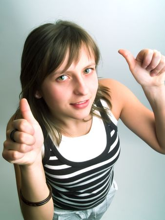 tolerate: A pretty blond girl viewed from above and she shows her thumbs betoken her approval