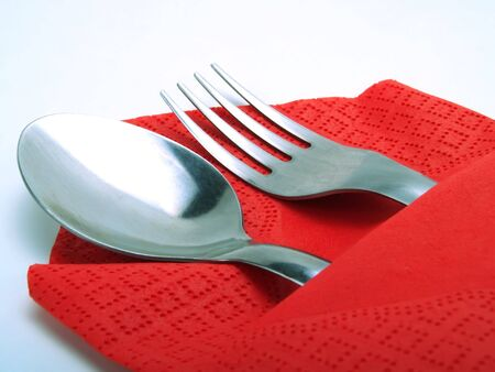 A nice place with a silvery spoon and fork, covered by a nice red napkin