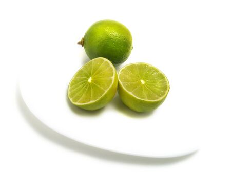 A group of half and whole fresh limes on white plate and isolated on white background Stock Photo - 3251925