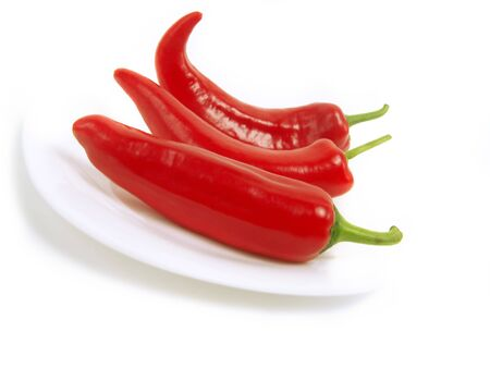 Three fresh red chili peppers on white plate and isolated on white background