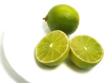 A group of half and whole fresh limes on white plate and isolated on white background Stock Photo - 3258687