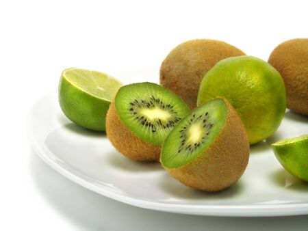 A group of fresh kiwis and limes on a white plate and isolated on white background Stock Photo - 3258689