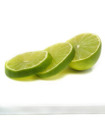 Sliced fresh lime on cutting board and isolated on white background Stock Photo - 3258679