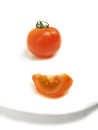 A slice of tomato and a blurred whole one on a white plate and isolated on white background  Stock Photo