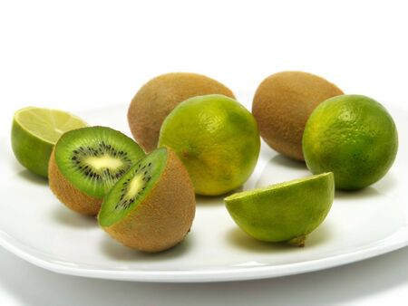A group of fresh kiwis and limes on a white plate and isolated on white background Stock Photo - 3294062
