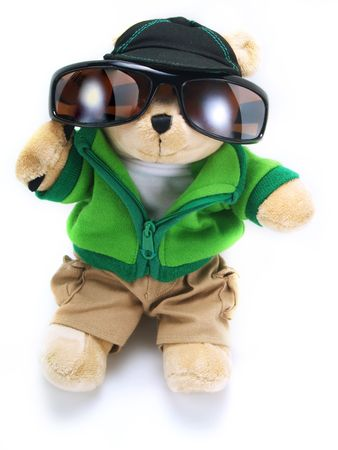 A little adorable teddy bear is wearing big sunglasses, a green jacket, brown pants, a hat and its isolated on white background.