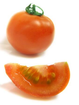 A slice of tomato and a blurred whole one isolated on white background