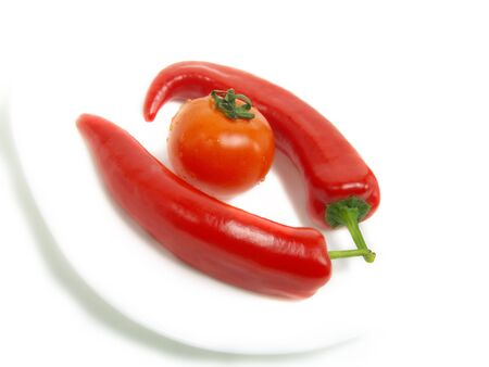 Two fresh chili peppers and a ripe tomato on a white plate and isolated on white background Stock Photo